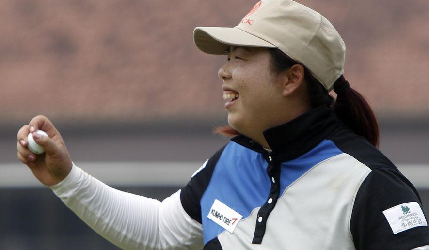 Shanshan Feng of China celebrates after winning the LPGA Malaysia golf tournament at Kuala Lumpur Golf and Country Club in Kuala Lumpur, Malaysia, Sunday, Oct. 12, 2014. (AP Photo/Lai Seng Sin)