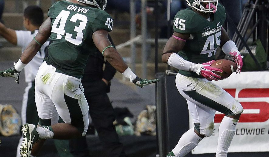 Michigan State linebacker Darien Harris (45) runs through the end zone after intercepting a pass and running it in for a touchdown in the fourth quarter of an NCAA college football game against Purdue in West Lafayette, Ind., Saturday, Oct. 11, 2014. Michigan State won 45-31. (AP Photo/AJ Mast)