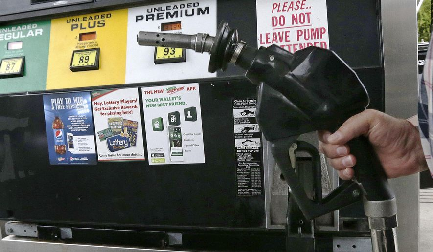 In this Sept. 30, 2014 photo, Dana Ripley, of Winthrop, Mass., fills the gas tank of his truck at a service station in Andover, Mass. In Ballot Question 1 in the Nov. 4 election, Massachusetts voters will have the opportunity to keep or repeal an automated yearly increase of the state gasoline tax. (AP Photo/Charles Krupa)