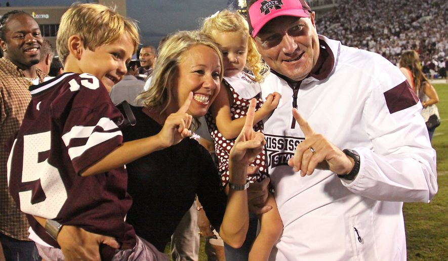 Mississippi State coach Dan Mullen and his family show they feel Mississippi State should be ranked No. 1 in the polls this week. With coach Mullen are his wife Megan and their children Canon, left and Breelyn, 2nd from right after his No. 3 Mississippi State team defeated No. 2 Auburn 38-23 in their NCAA college football game in Starkville, Miss., Saturday, Oct. 11, 2014. (AP Photo/Jim Lytle)