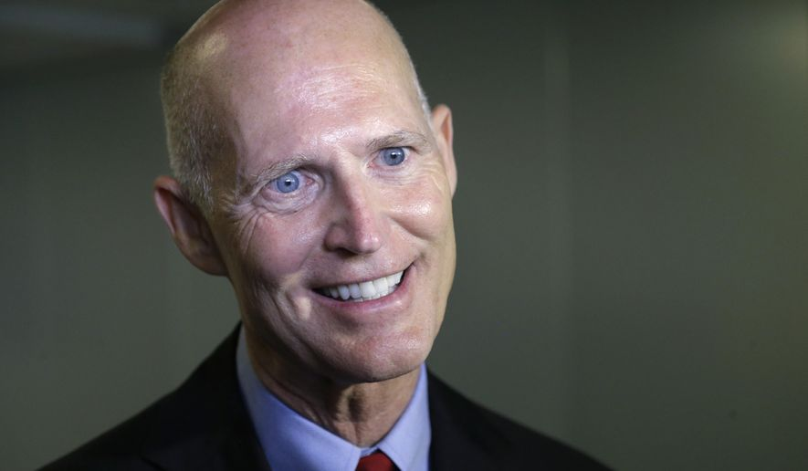 In this Sept. 22, 2014 photo, Florida Gov. Rick Scott speaks with members of the media in Miami. If former Florida Gov. Charlie Crist gets his old job back, he promises to expand Medicaid to roughly 1 million low-income residents by calling a special Legislative session or an executive order. If Gov. Rick Scott is re-elected, the decision will be once again left to the Legislature with little meddling from him. The Sunshine State has one of the highest uninsured rates in the country. (AP Photo/Wilfredo Lee)