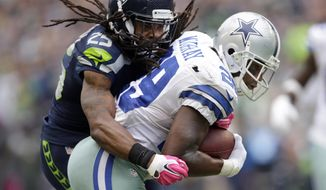 Dallas Cowboys running back DeMarco Murray, right, powers through a tackle by Seattle Seahawks cornerback Richard Sherman to score a touchdown in the second half of an NFL football game, Sunday, Oct. 12, 2014, in Seattle. (AP Photo/Scott Eklund)