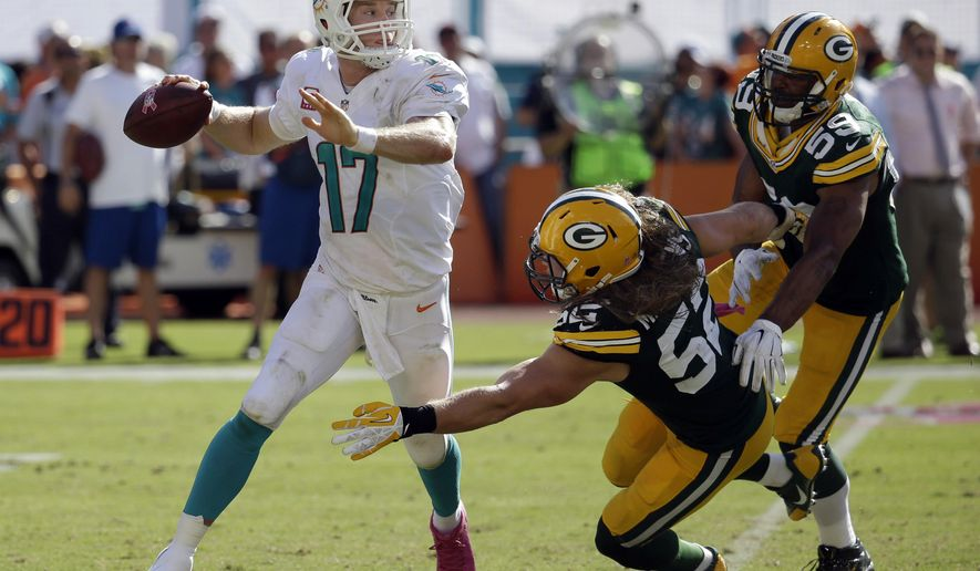 Miami Dolphins quarterback Ryan Tannehill (17) looks to throw the ball as he is pursued by Green Bay Packers outside linebackers Clay Matthews (52) and Brad Jones (59) during the second half of an NFL football game, Sunday, Oct. 12, 2014, in Miami Gardens, Fla. The Packers won 27-24. (AP Photo/Lynne Sladky)