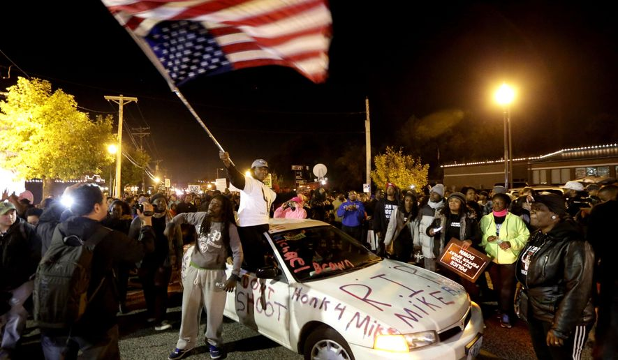 Protesters arrive at the Ferguson Police Department Saturday, Oct. 11, 2014, for a rally in remembrance of Michael Brown in Ferguson, Mo. On Aug. 9, 2014, a white police officer fatally shot the unarmed Brown, in the St. Louis suburb. (AP Photo/Charles Rex Arbogast)