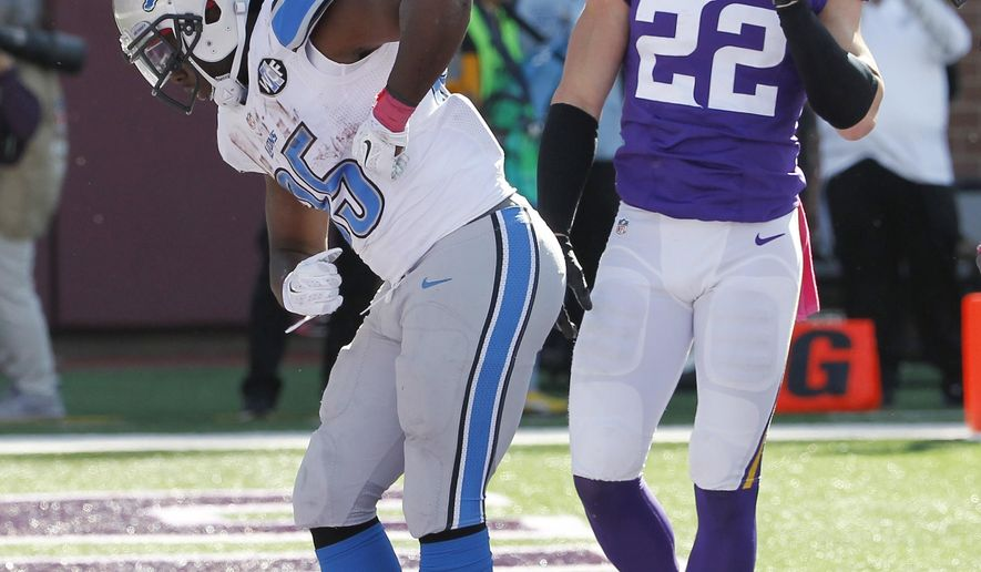Detroit Lions running back Joique Bell (35) celebrates in front of Minnesota Vikings free safety Harrison Smith (22) after scoring from the 1-yard line for a touchdown during the second half of an NFL football game Sunday, Oct. 12, 2014, in Minneapolis. (AP Photo/Ann Heisenfelt)