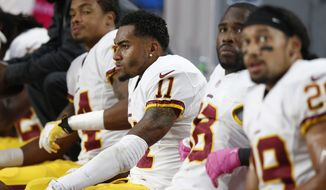 From left, Washington Redskins' Ryan Grant, DeSean Jackson, Pierre Garcon, and Roy Helu sit on the bench late in the second half of an NFL football game loss to the against the Arizona Cardinals Sunday, Oct. 12, 2014, in Glendale, Ariz.  The Cardinals defeated the Redskins 30-20. (AP Photo/Ross D. Franklin)
