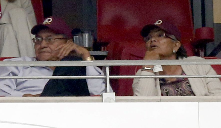 Navajo Nation president Ben Shelly and First Lady Martha Shelly wear Washington Redskins caps during the second half of an NFL football game against the Arizona Cardinals in Redskins owner Daniel Snyders' suite, Sunday, Oct. 12, 2014, in Glendale, Ariz.(AP Photo/Ross D. Franklin)