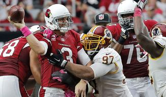 Arizona Cardinals quarterback Carson Palmer (3) gets the throw off as Washington Redskins defensive end Jason Hatcher (97) hits him during the second half of an NFL football game, Sunday, Oct. 12, 2014, in Glendale, Ariz. (AP Photo/Rick Scuteri)