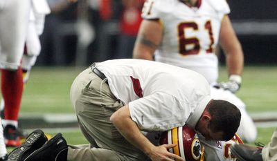 """Washington Redskins trainers attended to running back Clinton Portis after he received a concussion in the first quarter of a game in 2009. It's too early to determine the similarities and differences of brain trauma between veterans and football players, but Dr. Ann McKee, the chief of neuropathology in the VA Boston Healthcare System, says, """"I can tell you there are some parallels, and also some differences."""" (Associated Press)"""