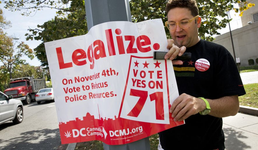 In this photo taken Oct. 9, 2014, Adam Eidinger, chairman of the DC Cannabis Campaign, puts up posters encouraging people to vote yes on DC Ballot Initiative 71 to legalize small amounts of marijuana for personal use, in Washington. Legalized weed would look far different in the nation's capital than it does in other places that have chosen to decriminalize marijuana. Even if voters approve it next month, as appears likely, it would remain banned in the roughly one-fourth of the District of Columbia that is federal land, so there would still be no lighting a joint in front of the Jefferson Memorial. The capital also remains under the thumb of Congress, which could quash legalization in D.C. regardless of what the voters want. (AP Photo/Jacquelyn Martin)