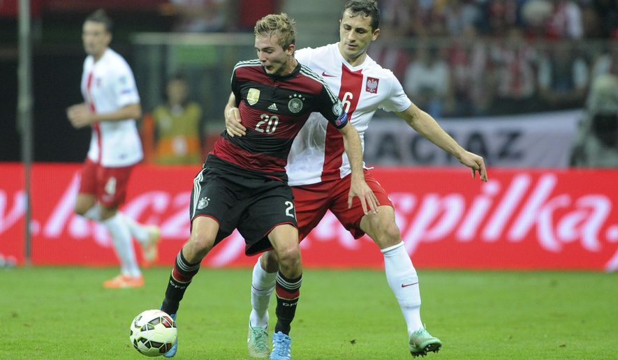 Germany's Christoph Kramer, left, is challenged by Poland's Tomasz Jodlowiec during a Euro 2016 group D qualifying soccer match between Poland and Germany in Warsaw, Poland, Saturday, Oct. 11, 2014. (AP Photo/Alik Keplicz)