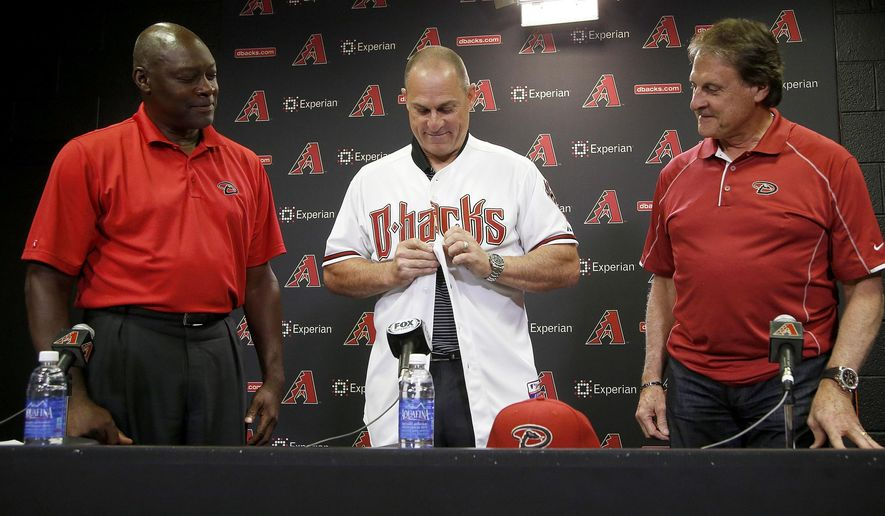 Arizona Diamondbacks baseball team new manager Chip Hale, middle, puts on a Diamondbacks jersey as he is introduced by general manager Dave Stewart, left, and  chief baseball officer Tony LaRussa during a news conference Monday, Oct. 13, 2014, in Phoenix.  The former Diamondbacks third base coach was hired Monday to replace fired  Kirk Gibson as the Diamondbacks manager.  The 49-year-old managed in Arizona's minor league system for six seasons and was with the Diamondbacks from 2007-09 in the first of eight consecutive seasons as a big league third base coach. (AP Photo/Ross D. Franklin) **FILE**