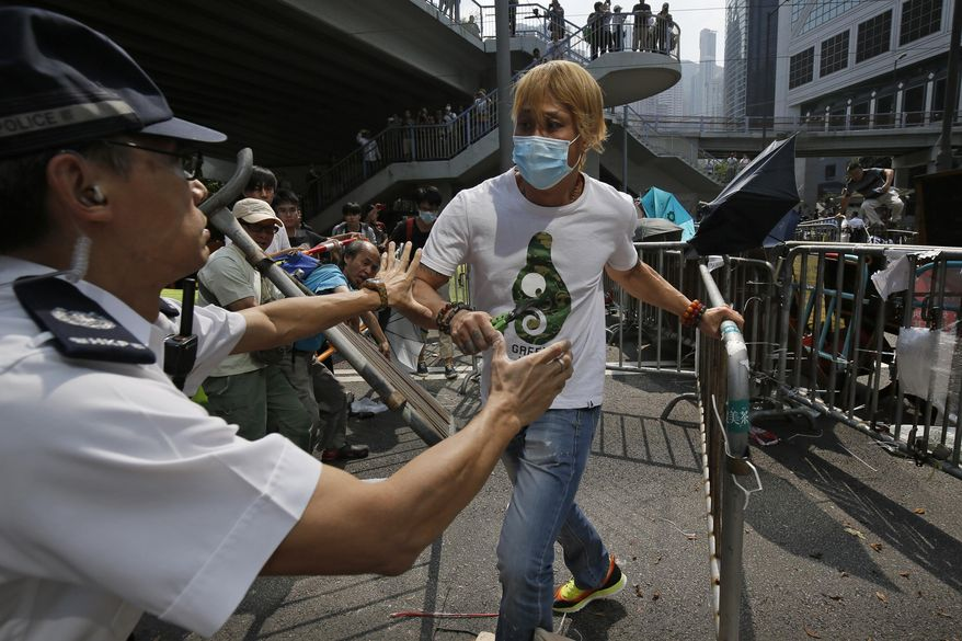 A police officer tries to stop a man who removing the metal barricades that protesters have set up to block off main roads near the heart of the city's financial district. Hong Kong Monday, Oct. 13, 2014. An angry crowd tried to charge barricades used by pro-democracy protesters to occupy part of downtown Hong Kong as a standoff with authorities dragged into a third week. (AP Photo/Vincent Yu)