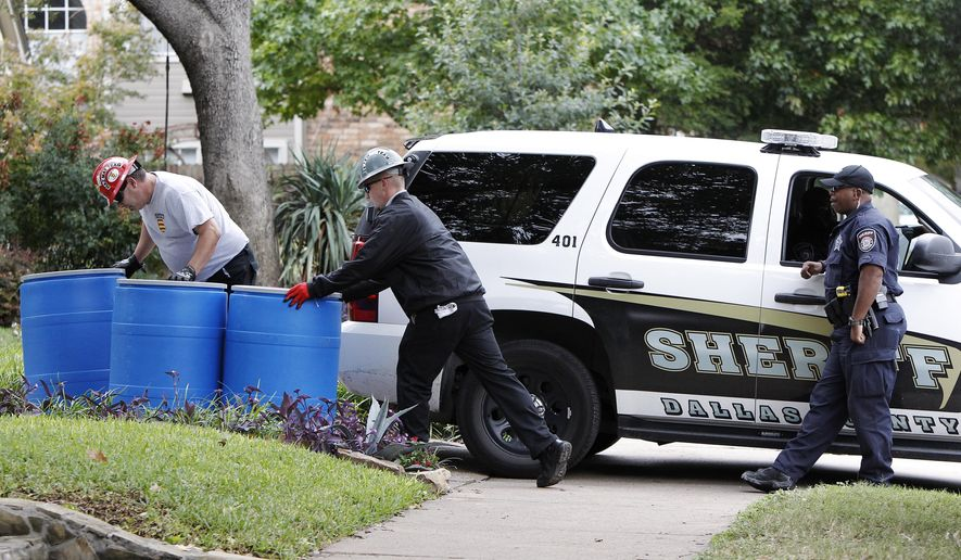 Protect Environmental workers move disposal barrels to a staging area outside the apartment of a healthcare worker who treated Ebola patient Thomas Eric Duncan and tested positive for the disease, Oct. 13, 2014, in Dallas. (AP Photo/Brandon Wade)