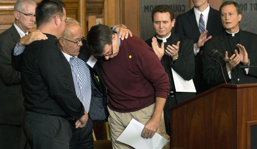 Attorney Jeff Anderson gives a hug to abuse survivors Jim Keenan, left, and Al Michaud, in red, after they both spoke of the importance of this historic agreement during a news conference in St. Paul, Minn., Monday, Oct. 13, 2014. A Minnesota judge signed off on a settlement in a groundbreaking case that accused Catholic church leaders in Minnesota of creating a public nuisance by failing to warn parishioners about an abusive priest. (AP Photo/The Star Tribune, Brian Mark Peterson)