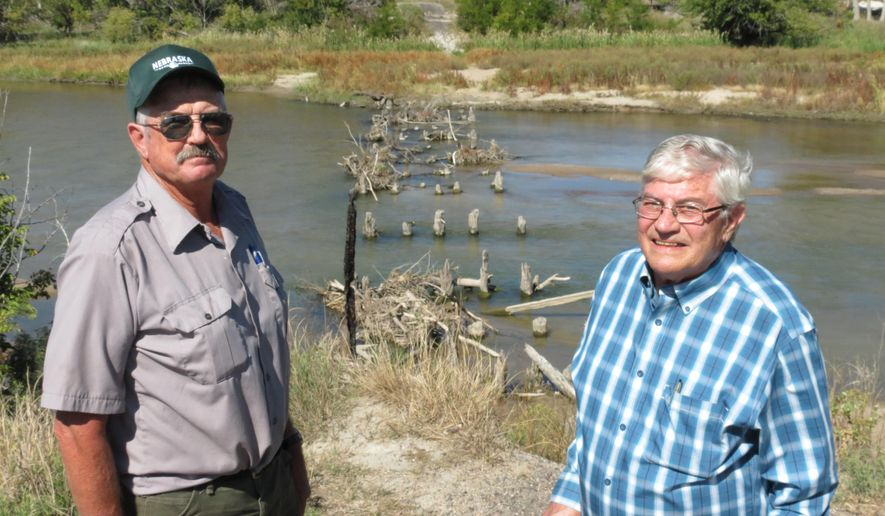 In this September 30, 2014 photo, Fort Kearny State Park Superintendent Gene Hunt, left, and Bill Berryman, of Kearney, pose for a photo along the Fort Kearny Hike-Bike Trail on the bank of the Platte River's north channel in Kearney, Neb. Hunt and Berryman are excited to see work start this fall to install a new bridge to replace the old wooden railroad bridge destroyed by a 2009 wildfire. (AP Photo/The Daily Hub, Lori Potter)
