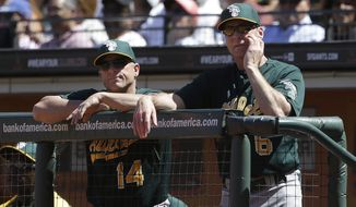 Oakland Athletics bench coach Chip Hale (14) and manager Bob Melvin (6) watch from the dugout during a baseball game against the San Francisco Giants in San Francisco, Thursday, May 30, 2013. The Giants won 5-2. (AP Photo/Jeff Chiu)