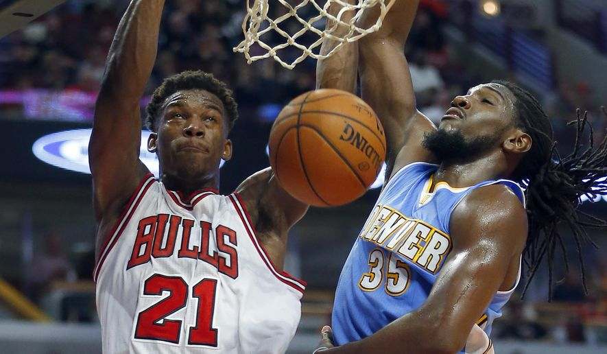 Chicago Bulls guard Jimmy Butler (21) dunks in front of Denver Nuggets forward Kenneth Faried (35) during the second half of a pre-season NBA basketball game in Chicago, on Monday Oct. 13, 2014. The Bulls won the game 110-90. (AP Photo/Jeff Haynes)