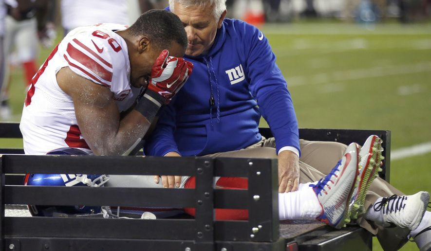 FILE - In this Oct. 12, 2014, file photo, New York Giants wide receiver Victor Cruz, left, is carted off the field during the second half of an NFL football game against the Philadelphia Eagles in Philadelphia. Down two games in the NFC East, the Giants face the prospect of playing the rest of the season without Cruz, who sustained a knee injury. (AP Photo/Matt Rourke, File)