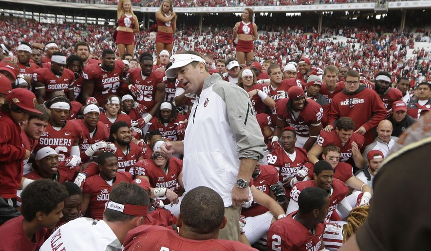 Oklahoma head coach Bob Stoops speaks to his team after an NCAA college football game against Texas, Saturday, Oct. 11, 2014, in Dallas. Oklahoma won 31-26. (AP Photo/LM Otero)