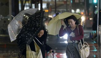 Travelers struggle with umbrellas in the heavy rain and strong wind caused by Typhoon Vongfong in front of Nagoya Station in Nagoya, central Japan, Monday, Oct. 13, 2014. (AP Photo/Kyodo News)