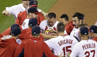 St. Louis Cardinals' Kolten Wong is congratulated after hitting a walk off home run during the ninth inning in Game 2 of the National League baseball championship series against the San Francisco Giants Sunday, Oct. 12, 2014, in St. Louis. The Cardinals won 5-4 to tie the series at 1-1. (AP Photo/Charlie Neibergall)