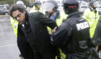 Philosopher Cornel West, center, is taken into custody after performing an act of civil disobedience at the Ferguson, Missouri, police station Monday as hundreds continue to protest the fatal shooting of 18-year-old Michael Brown by police in August. (AP Photo/Charles Rex Arbogast)