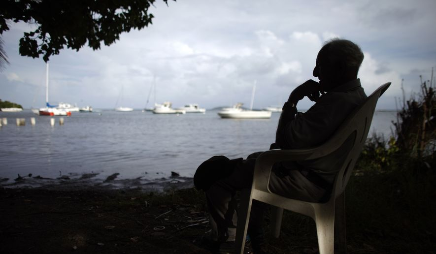 A man sits in a chair in front of a beach as Hurricane Gonzalo approaches to the area in Fajardo, Puerto Rico, Monday, Oct. 13, 2014. Hurricane Gonzalo formed Monday in the Caribbean and was on course to move out over open ocean after buffeting Antigua and nearby islands with heavy rain and wind. (AP Photo/Ricardo Arduengo)