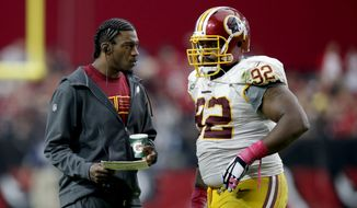 Washington Redskins quarterback Robert Griffin III talks with Chris Baker (92) during the second half of an NFL football game against  the Arizona Cardinals, Sunday, Oct. 12, 2014, in Glendale, Ariz.(AP Photo/Ross D. Franklin)