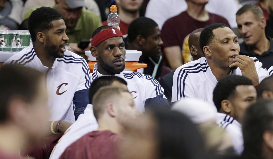 Cleveland Cavaliers' LeBron James, center, watches the NBA basketball game against the Milwaukee Bucks from the bench during the second quarter Tuesday, Oct. 14, 2014, in Cleveland. (AP Photo/Tony Dejak)