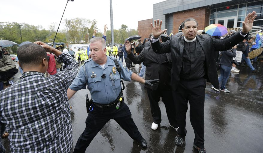 A police officer tries to keep protesters from advancing farther into the parking lot at the Ferguson, Mo., police station, Monday, Oct. 13, 2014. Activists have planed a day of civil disobedience to protest the shooting of Michael Brown in August and a second police shooting in St. Louis last week. (AP Photo/Charles Rex Arbogast)