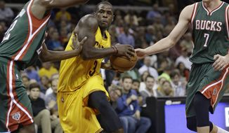 Cleveland Cavaliers' Dion Waiters (3) drives between Milwaukee Bucks' Kris Middleton (22) and Ersan Ilyasova (7) during the second quarter of an NBA preseason basketball game Tuesday, Oct. 14, 2014, in Cleveland. (AP Photo/Tony Dejak)
