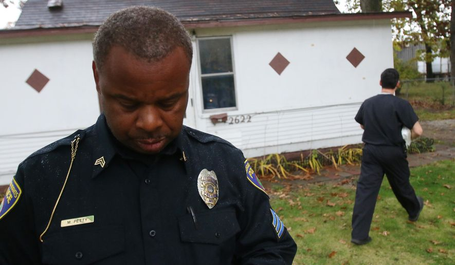 Muskegon Heights police Sgt. Marvin Petty looks at his phone as he works at the scene of a possible homicide on the morning of Tuesday, Oct. 14, 2014.  Medical examiner Chris Anderson walks to toward the home in the background.  Judy Bushman, 62, was discovered inside this residence. (AP Photo/The Muskegon Chronicle, Ken Stevens)