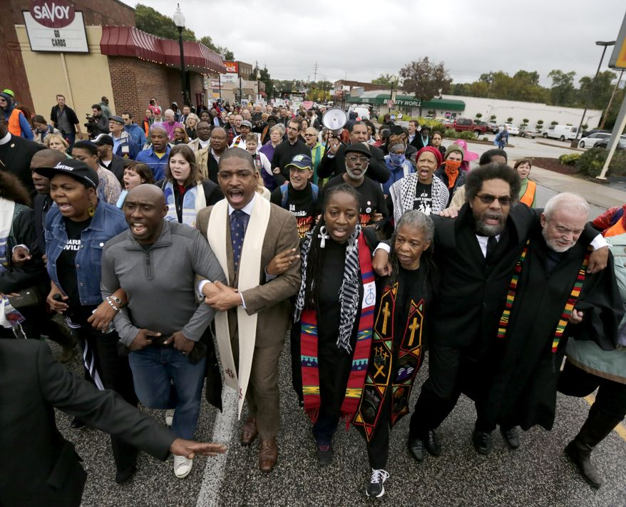 Protesters, including Cornel West, second from right, march to the Ferguson, Mo., police station, Monday, Oct. 13, 2014, in Ferguson. Activists planned a day of civil disobedience to protest the shooting of Michael Brown, in August, and a second police shooting in St. Louis last week. (AP Photo/Charles Rex Arbogast)
