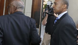 Former Charlotte Mayor Patrick Cannon, right, arrives at the federal courthouse in Charlotte, N.C., Tuesday, Oct. 14, 2014, for sentencing in his corruption case. (AP Photo/Chuck Burton)