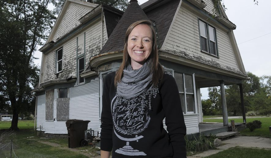 In this Tuesday, Sept. 30, 2014 photo, Jessica Concannon, principal at River of Life School is working to rehab a house at 332 Broadway Ave., in Benton Harbor, Mich., to become the Women's Ministry House for Forefront Street Ministries. (AP Photo/The Herald-Palladium, Don Campbell)