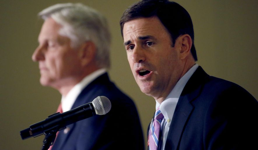 Arizona Republican gubernatorial candidate Doug Ducey speaks as democratic candidate Fred DuVal listens, Tuesday, Oct 13, 2014 during a debate for the Arizona Women's Forum in Scottsdale, Ariz. (AP Photo/Matt York)