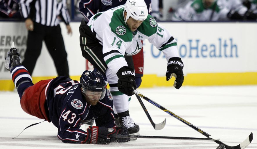 Dallas Stars' Jamie Benn, right, works for the puck against Columbus Blue Jackets' Scott Hartnell during the first period of an NHL hockey game in Columbus, Ohio, Tuesday, Oct. 14, 2014. (AP Photo/Paul Vernon)