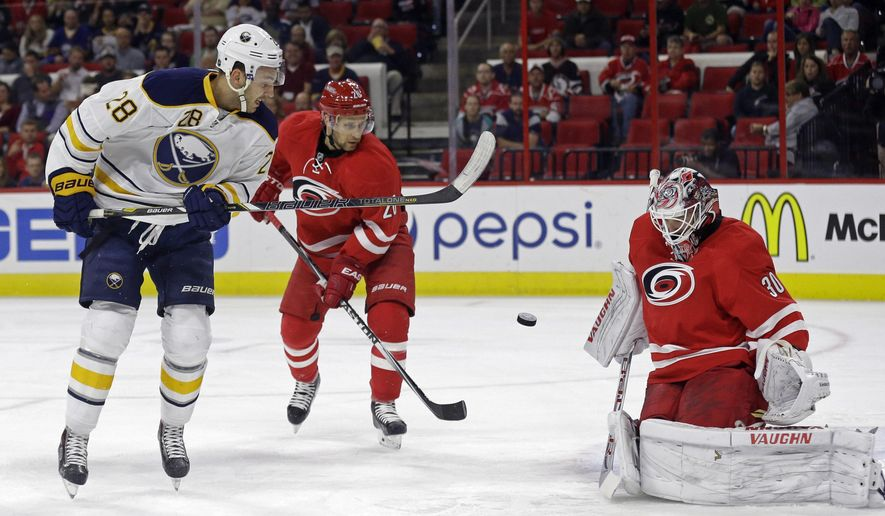 Carolina Hurricanes goalie Cam Ward (30) and Hurricanes' John-Michael Liles (26) defend the goal against Buffalo Sabres' Zemgus Girgensons (28), of Latvia, during the first period of an NHL hockey game in Raleigh, N.C., Tuesday, Oct. 14, 2014. (AP Photo/Gerry Broome)