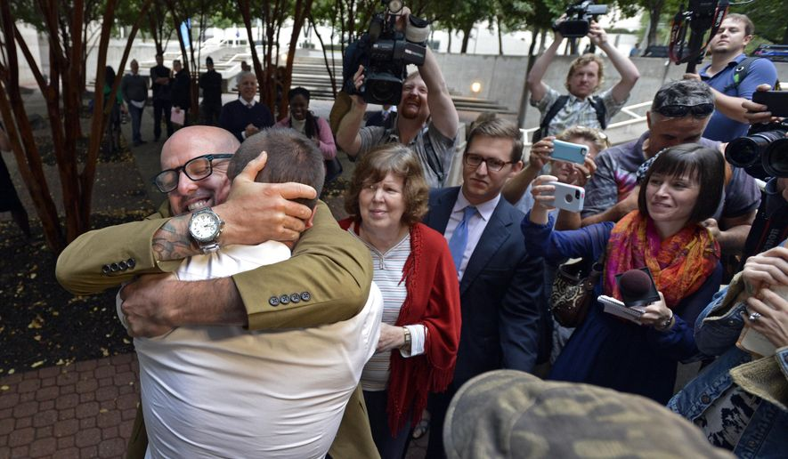 The scene outside the Mecklenburg County's Register of Deeds office as Joey Hewell and Scott Lindsley embrace after being married Monday, Oct. 13, 2014, in Charlotte, N.C. (AP Photo/The Charlotte Observer, Davie Hinshaw)