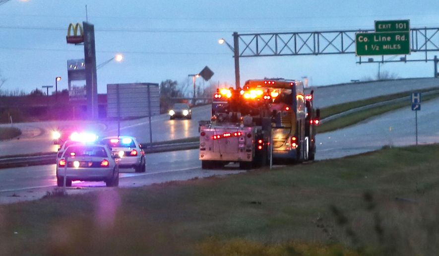 A double decker bus is towed north on I-65 in Greenwood, Ind., after the bus overturned early Tuesday, Oct. 14, 2014 after apparently swerving to avoid a minor crash, badly injuring one person and hurting more than a dozen others, officials said. The bus operated by the Megabus line was traveling from Atlanta to Chicago, said Sean Hughes, a spokesman for the line's parent company, Coach USA North America. (AP Photo/The Indianapolis Star, Kelly Wilkinson)  NO SALES