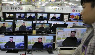 A shopper passes by TV monitors displaying a news program at an electronic shop in Seoul, South Korea, Tuesday, Oct. 14, 2014, showing a photo of North Korean leader Kim Jong-un smiling, reportedly during his first public appearance in five weeks in Pyongyang, North Korea. (AP Photo/Ahn Young-joon)