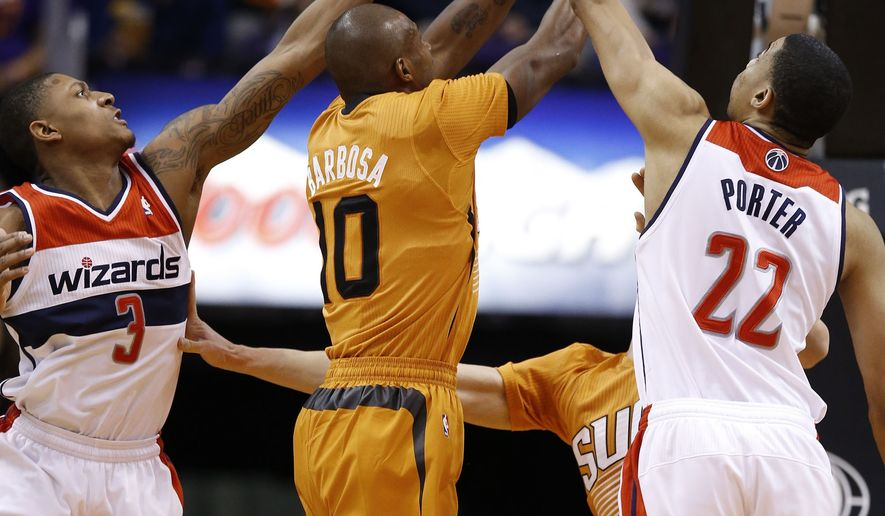 Phoenix Suns' Leandro Barbosa (10), of Brazil, tries to get past the defense of Washington Wizards' Bradley Beal (3) and Otto Porter Jr. (22) during the first half of an NBA basketball game Friday, Jan. 24, 2014, in Phoenix.  The Wizards defeated the Suns 101-95. (AP Photo/Ross D. Franklin)