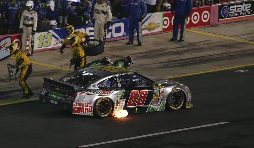 A ball of fire shoots from the back of Dale Earnhardt Jr.'s (88) car as his crew pushes him off pit road during the NASCAR Sprint Cup series Bank of America 500 auto race at Charlotte Motor Speedway in Concord, N.C., Saturday, Oct. 11, 2014. (AP Photo/Chris Keane)