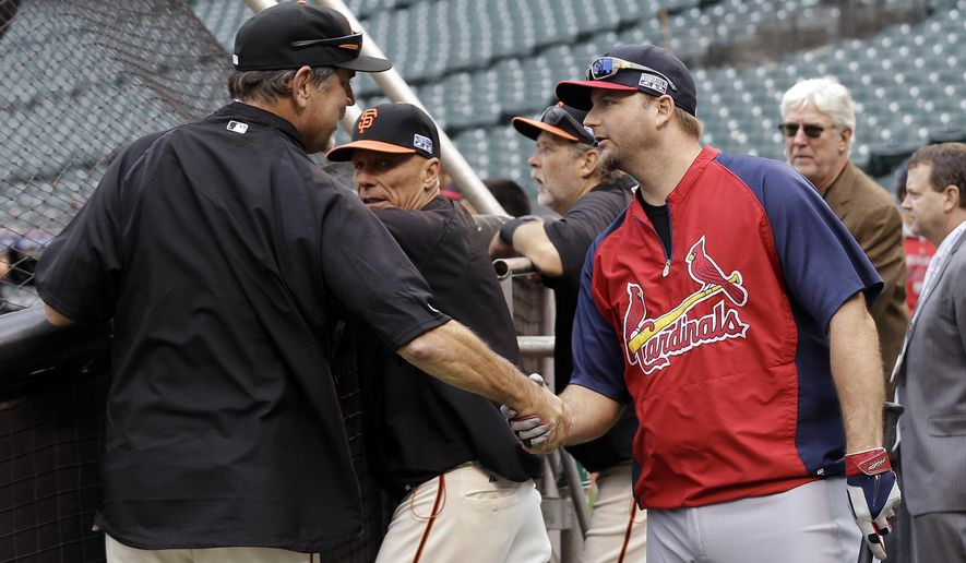San Francisco Giants manager Bruce Bochy, left, and St. Louis Cardinals catcher A.J. Pierzynski chat before Game 3 of the National League baseball championship series Tuesday, Oct. 14, 2014, in San Francisco. (AP Photo/Jeff Chiu)