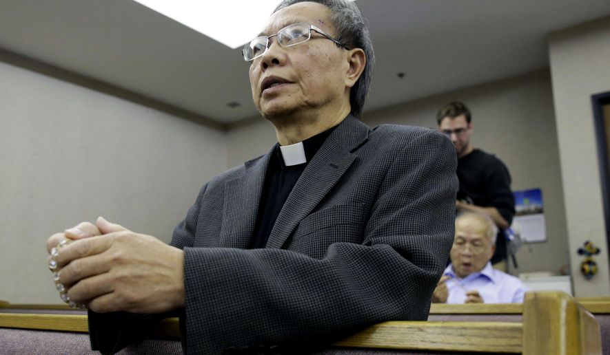 Father Jim Khoi prays the rosary at the Our Lady of Fatima Church where the family of nurse Nina Pham attend, Monday, Oct. 13, 2014, in Fort Worth, Texas. Pham, 26, became the first person to contract Ebola within the United States. (AP Photo/LM Otero)