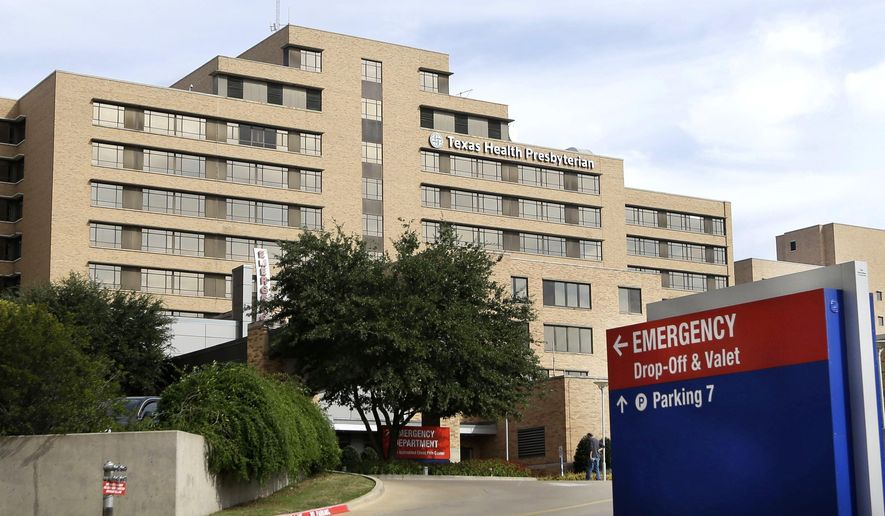 In this Oct. 8, 2014, file photo, a sign points to the entrance to the emergency room at Texas Health Presbyterian Hospital Dallas, where U.S. Ebola patient Thomas Eric Duncan was being treated, in Dallas. About 70 staff members at Texas Health Presbyterian Hospital were involved in the care of Thomas Eric Duncan after he was hospitalized, including a nurse now being treated for the same Ebola virus that killed the Liberian man who was visiting Dallas, according to medical records his family provided to The Associated Press. (AP Photo/LM Otero, File)