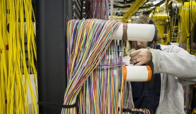 In a Friday, Oct. 3, 2014, file photo, U.S. Internet employee Tim Mattis separates fiber optic cables from one another, at U.S. Internet's southwest central office in Minneapolis. (AP Photo/MPR News, Bridget Bennett) ** FILE **