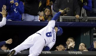 Kansas City Royals third baseman Mike Moustakas makes a catch on a ball hit by Baltimore Orioles' Adam Jones during the sixth inning of Game 3 of the American League baseball championship series Tuesday, Oct. 14, 2014, in Kansas City, Mo. (AP Photo/Charlie Riedel)