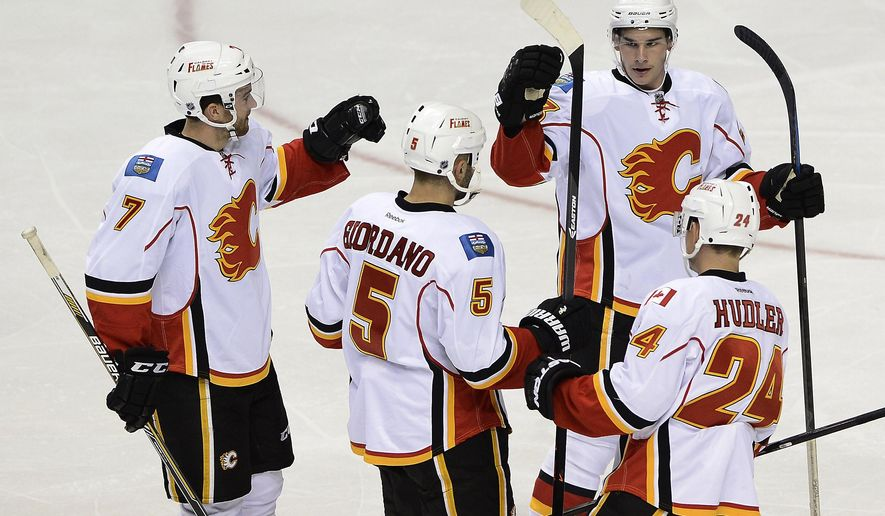 Calgary Flames defenseman Mark Giordano (5) is congratulated by defenseman T.J. Brodiein (7), center Sean Monahan (23), and left wing Jiri Hudler (24), of the Czech Republic, after Giordano scored against the Nashville Predators in the second period of an NHL hockey game Tuesday, Oct. 14, 2014, in Nashville, Tenn. (AP Photo/Mark Zaleski)